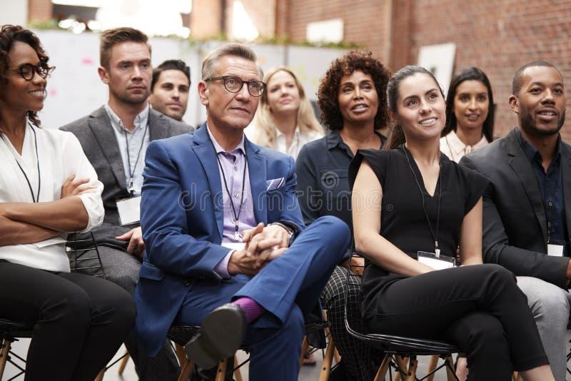 Gruppo di uomini d'affari e di donne di affari che ascoltano la presentazione alla conferenza fotografia stock