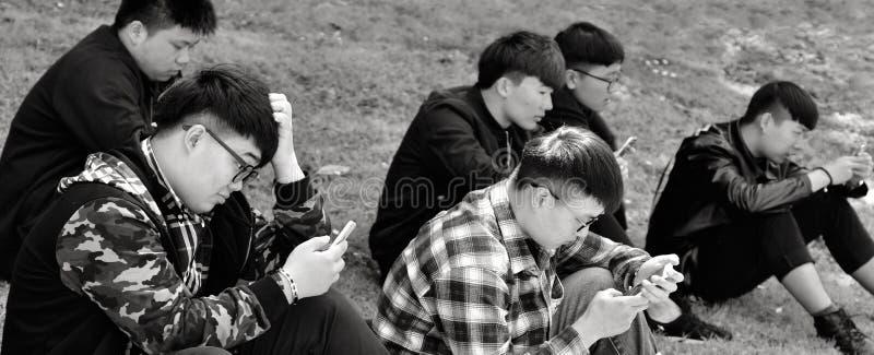 Gruppo di uomini di Chines che per mezzo dei loro telefoni cellulari all'aperto immagini stock libere da diritti
