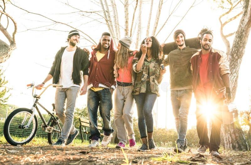 Gruppo di gruppo urbano degli amici che cammina nel parco del pattino della città fotografie stock