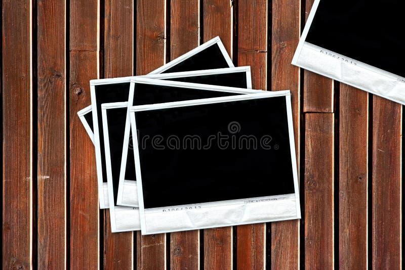 Gruppo di vecchi polaroids in bianco sopra priorità bassa di legno fotografia stock libera da diritti