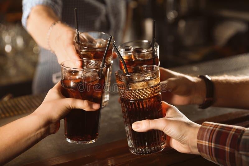 Gruppo di vetri tintinnanti degli amici con cola alla tavola all'interno fotografie stock libere da diritti