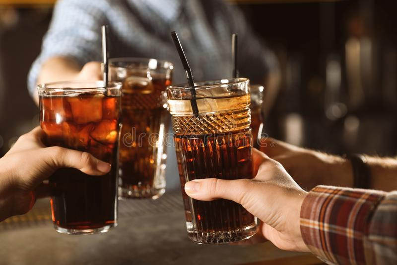 Gruppo di vetri tintinnanti degli amici con cola alla tavola, primo piano immagini stock