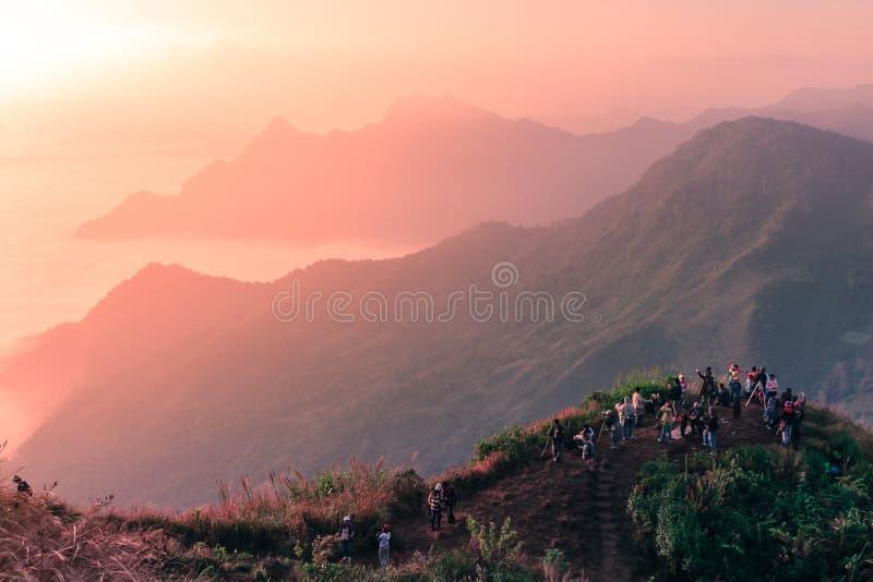 Gruppo di viaggiatore che sta sopra la montagna per vedere e catturare la scena di alba immagini stock libere da diritti