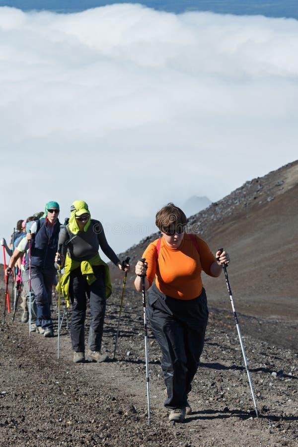Gruppo di viaggiatori delle donne che scalano al vulcano immagine stock