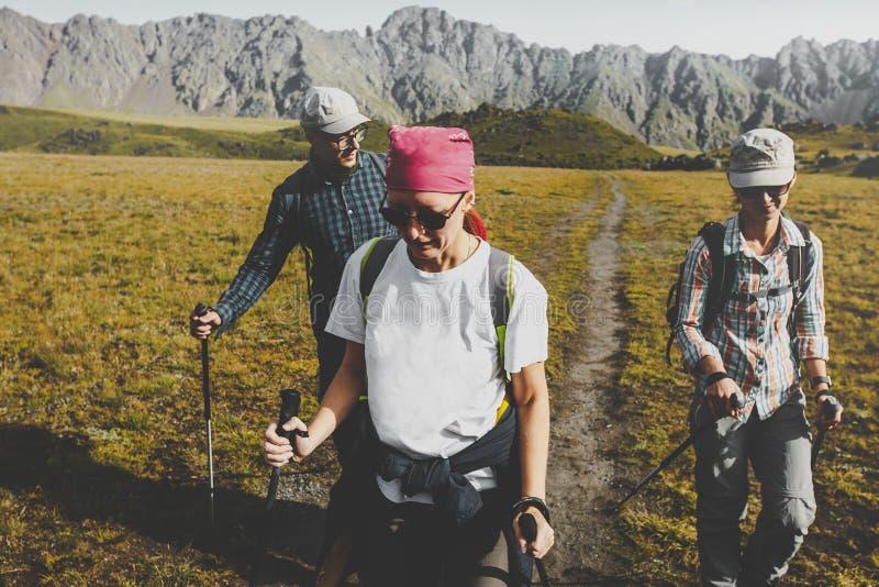Gruppo di viandanti che camminano lungo la pianura in montagne di estate, concetto di viaggio di viaggio di viaggio fotografia stock libera da diritti