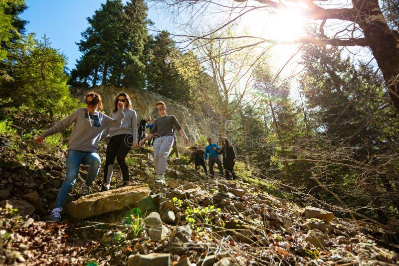 Gruppo di viandanti che camminano su una montagna al tramonto immagini stock libere da diritti