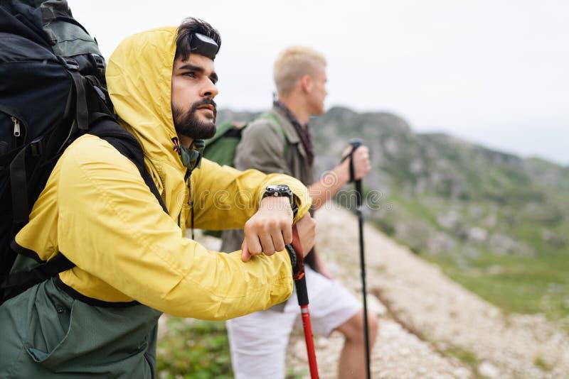 Gruppo di viandanti degli amici che camminano su una montagna al tramonto immagini stock