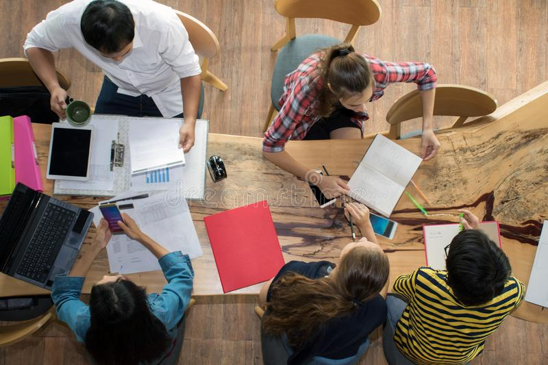 Gruppo di vista superiore di amici adolescenti da essere occupati lavorare in gruppo con i rapporti e computer portatile all'univ fotografie stock libere da diritti