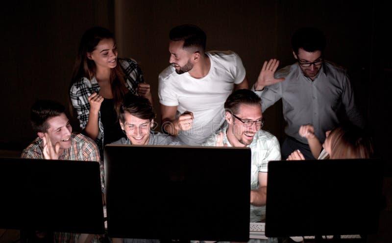 Gruppo felice di affari che esamina gli schermi di computer immagine stock
