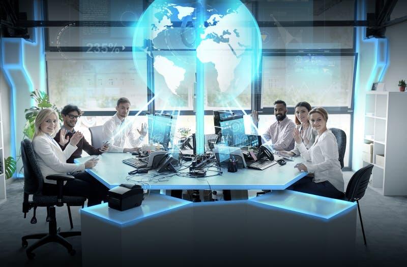 Gruppo felice di affari con l'ologramma della terra all'ufficio fotografie stock libere da diritti