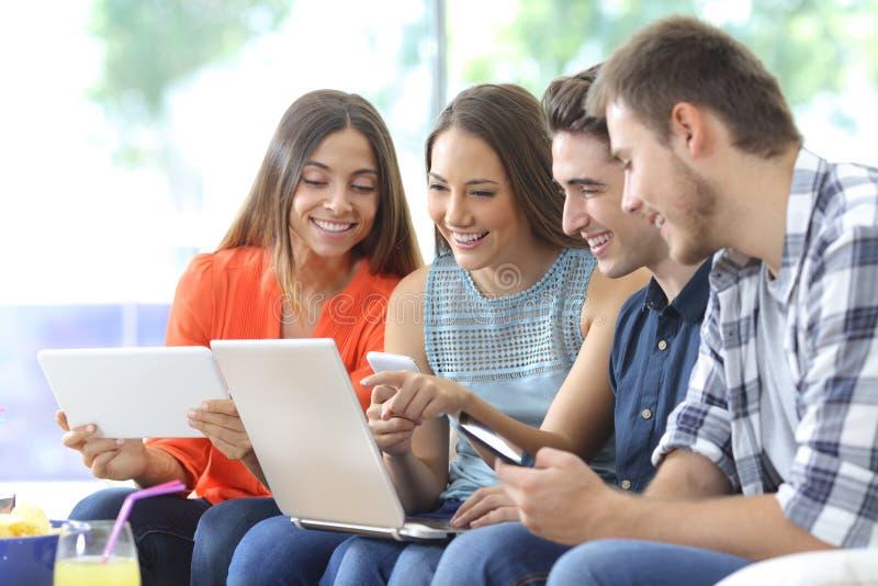 Gruppo felice di amici che controllano i dispositivi multipli fotografia stock