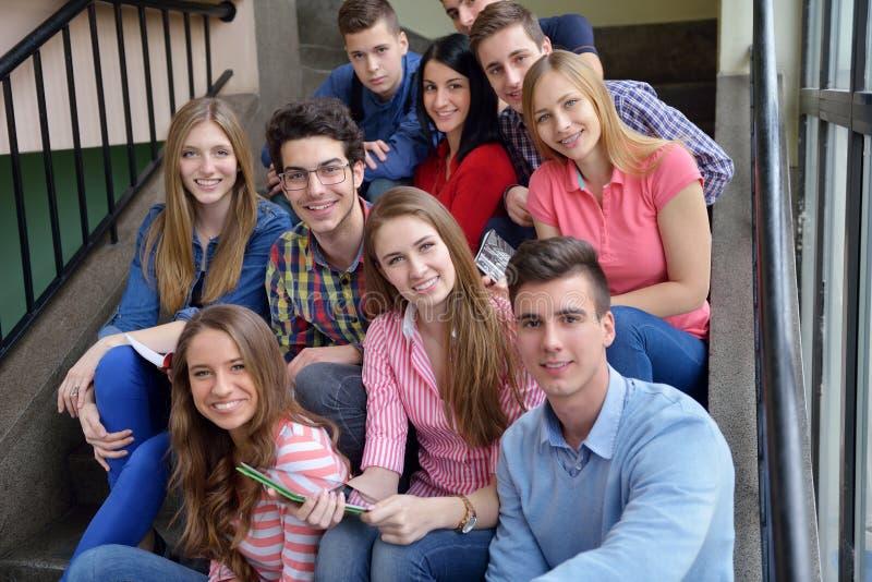 Gruppo felice di anni dell'adolescenza a scuola fotografia stock