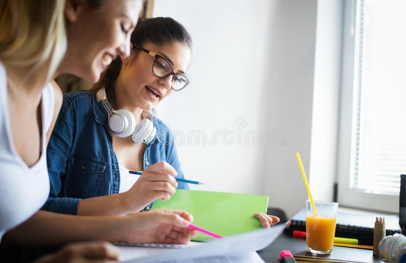 Gruppo felice di studenti che studiano insieme e che imparano nell'istituto universitario fotografia stock libera da diritti