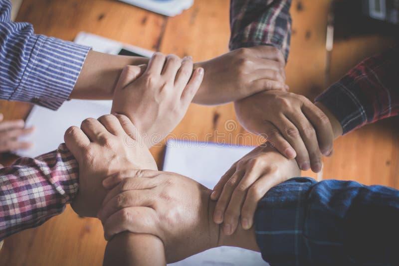 Gruppo giovane che mette le mani su per la nuova partenza nell'ufficio creativo, nel Co-lavoro di Team Teamwork Togetherness Coll fotografia stock