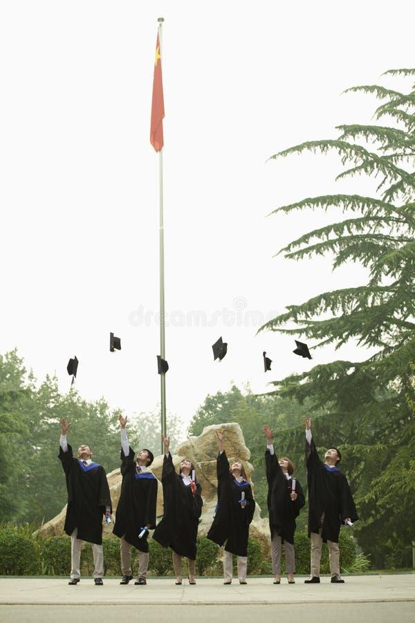 Gruppo giovane di laureati dell'università che gettano i tocchi nell'aria, verticale fotografie stock libere da diritti