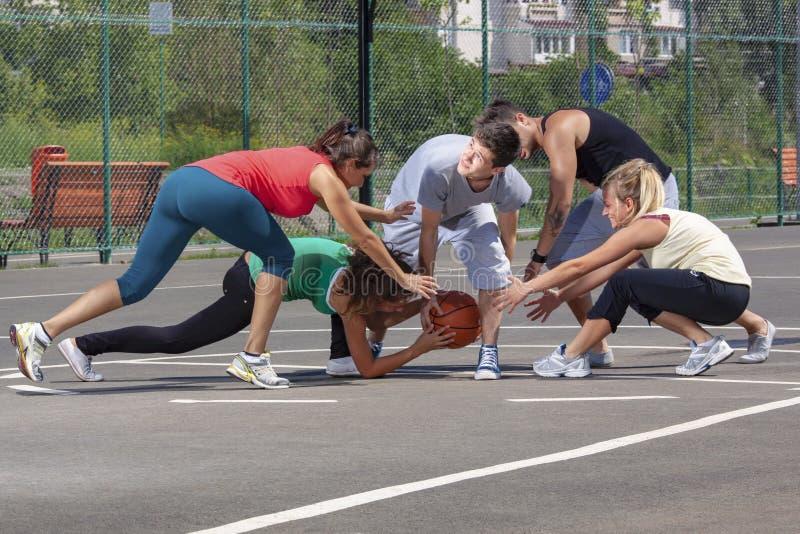 Gruppo giovane misto che gioca pallacanestro su un campo da giuoco immagini stock libere da diritti