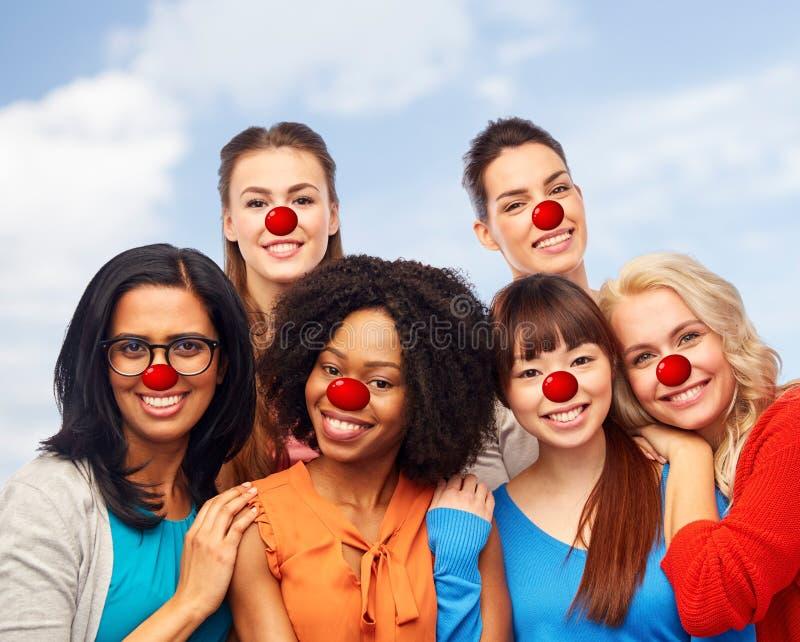 Gruppo internazionale di donne felici al giorno rosso del naso fotografie stock