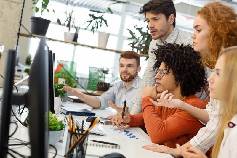 Gruppo millenario che lavora con il nuovo progetto sullo schermo di computer immagini stock libere da diritti