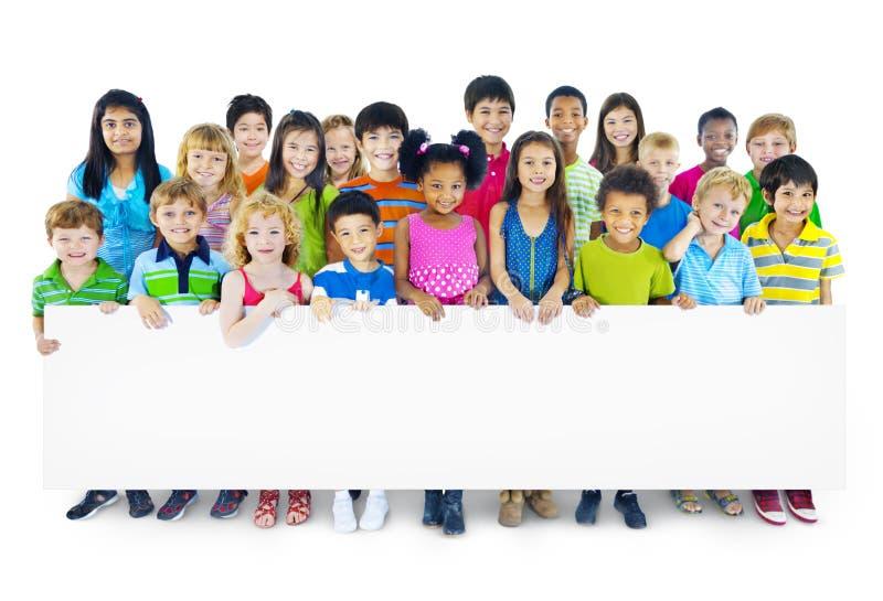 Gruppo Multi-etnico di bambini che tengono tabellone per le affissioni vuoto fotografia stock libera da diritti