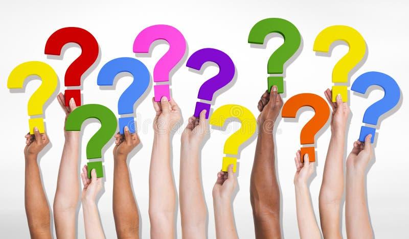 Gruppo Multi-etnico di mani umane che tengono i punti interrogativi immagini stock libere da diritti