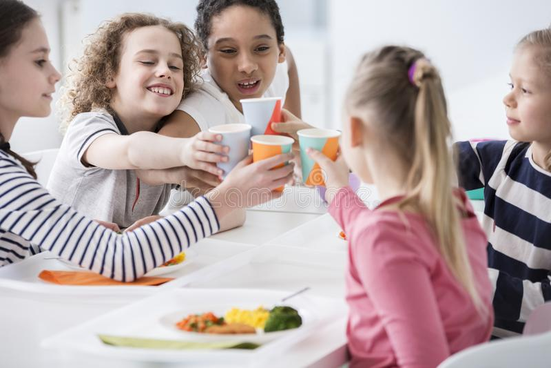 Gruppo multiculturale di bambini che tostano durante la festa di compleanno a fotografia stock