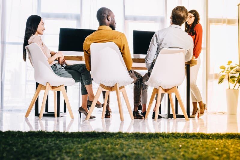 gruppo multiculturale di gente di affari che ha riunione nel luogo di lavoro immagini stock libere da diritti