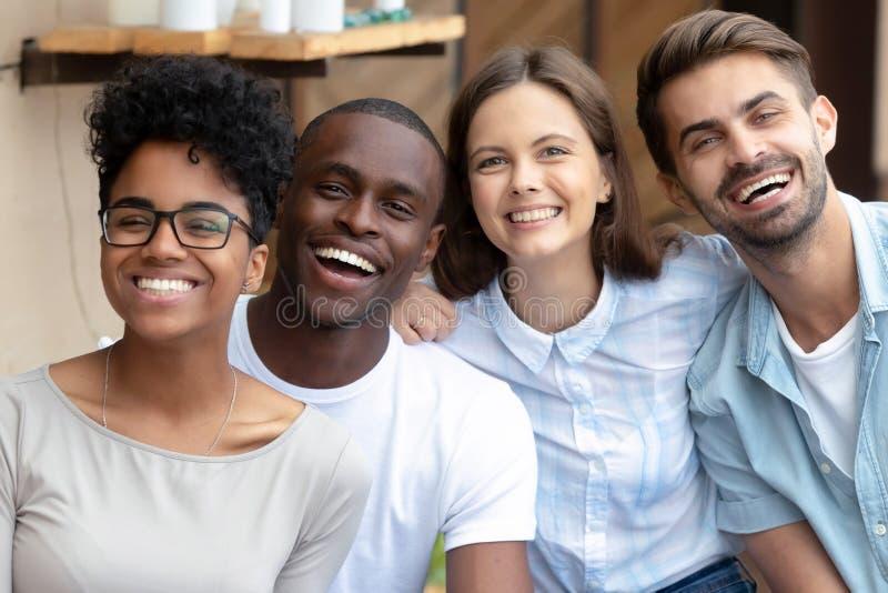 Gruppo multiculturale felice degli amici che ride esaminando macchina fotografica, ritratto fotografia stock