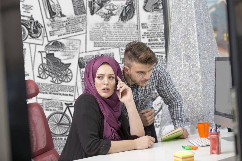 Gruppo multiculturale internazionale sul lavoro: donna musulmana asiatica ed uomo caucasico fotografia stock libera da diritti