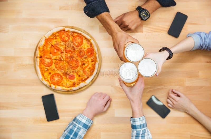 Gruppo multietnico di birra dei giovani e di pizza beventi di cibo immagini stock