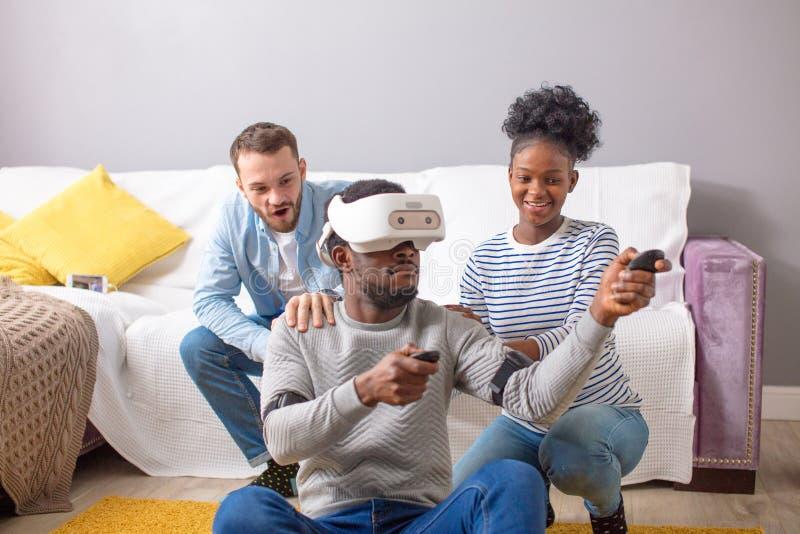 Gruppo multirazziale di amici divertendosi che prova sugli occhiali di protezione di realt? virtuale 3D immagine stock libera da diritti