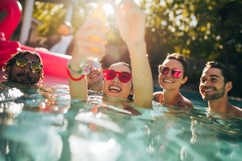 Gruppo multirazziale di amici divertendosi in uno stagno immagine stock libera da diritti