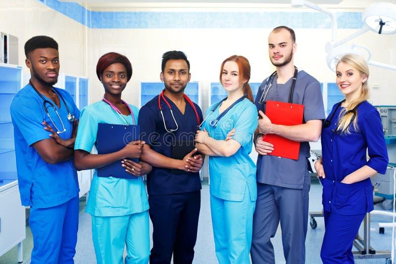 Gruppo multirazziale di giovani medici in un ospedale che sta in una sala operatoria immagine stock libera da diritti