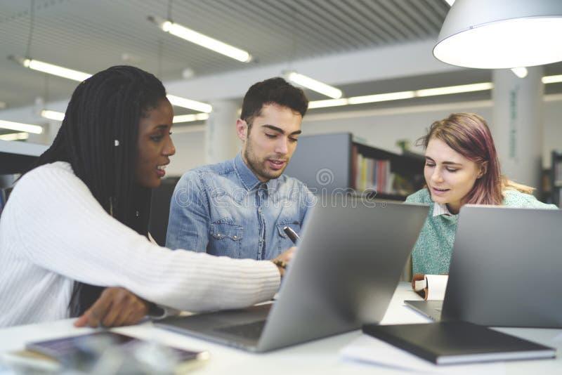 Gruppo multirazziale di lavorare di collaborazione degli studenti internazionali al progetto in biblioteca universitaria immagini stock
