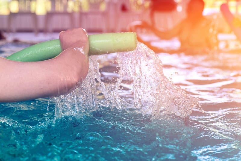 Gruppo o giovani e senior nell'esercitazione aquarobic della piscina di forma fisica fotografia stock libera da diritti
