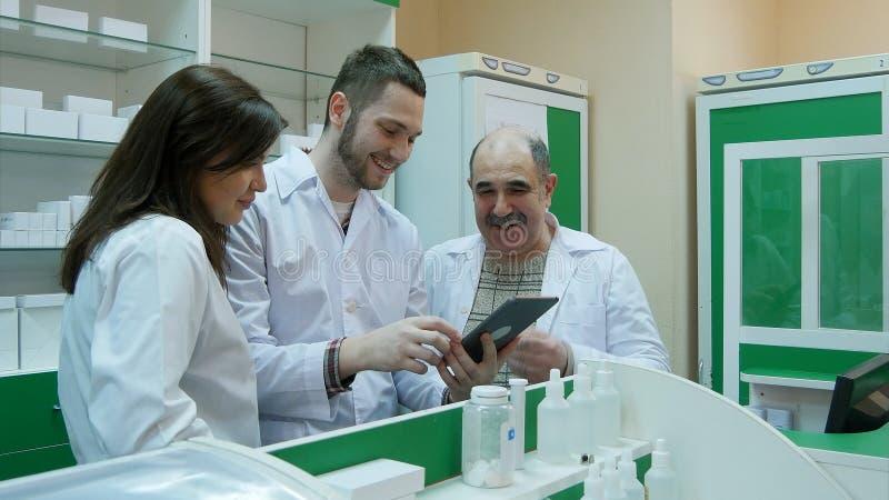 Gruppo positivo del farmacista che per mezzo del pc della compressa alla farmacia fotografia stock