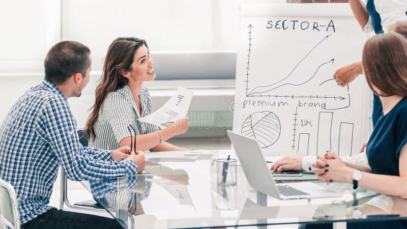 Gruppo professionale di affari che discute gli schemi di vendita alla riunione di lavoro fotografia stock