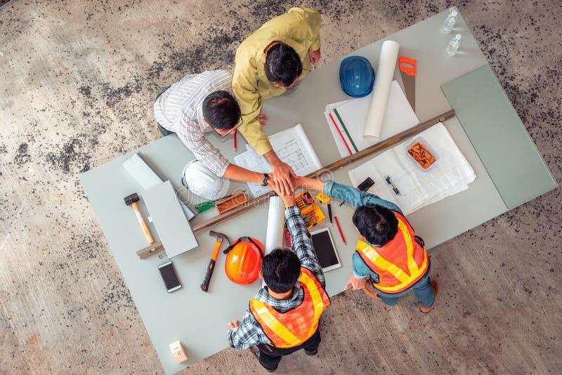 Gruppo professionale di ingegneria che stringe insieme le mani per l'unità t fotografie stock
