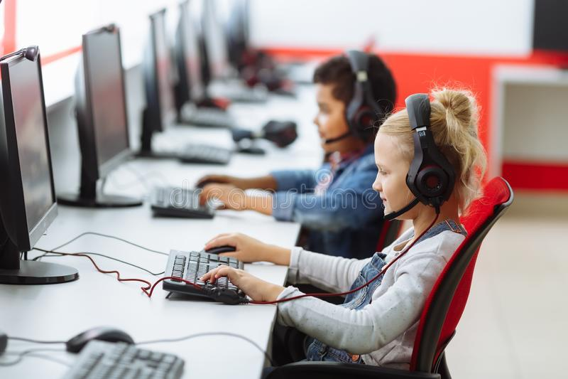 Gruppo razziale misto di bambini della scuola elementare nella classe del computer immagini stock libere da diritti