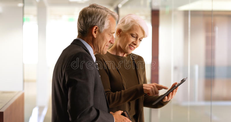 Gruppo senior di affari che supera i dati finanziari sulla compressa nel corridoio fotografia stock