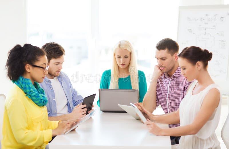 Gruppo serio con il pc ed il computer portatile della tavola in ufficio immagine stock libera da diritti