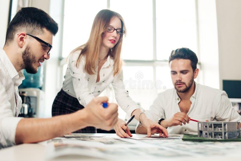 Gruppo sicuro degli ingegneri che lavorano insieme in uno studio dell'architetto immagine stock libera da diritti