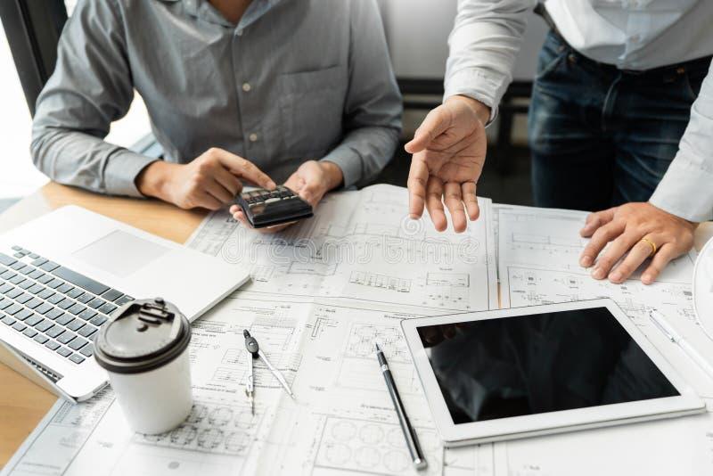 Gruppo sicuro dell'ingegnere che lavora con la stampa blu con il progetto di costruzione di discussione e di progettazione dell'a fotografia stock