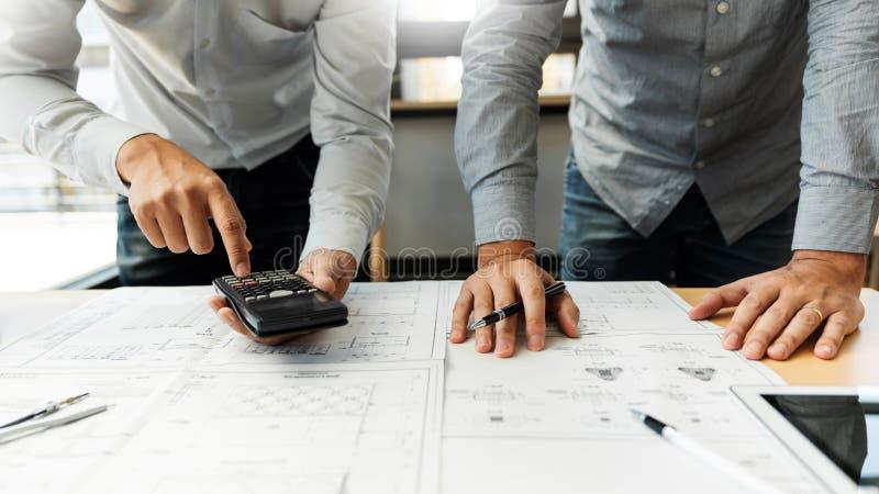 Gruppo sicuro dell'ingegnere che lavora con la stampa blu con il progetto di costruzione di discussione e di progettazione dell'a immagine stock