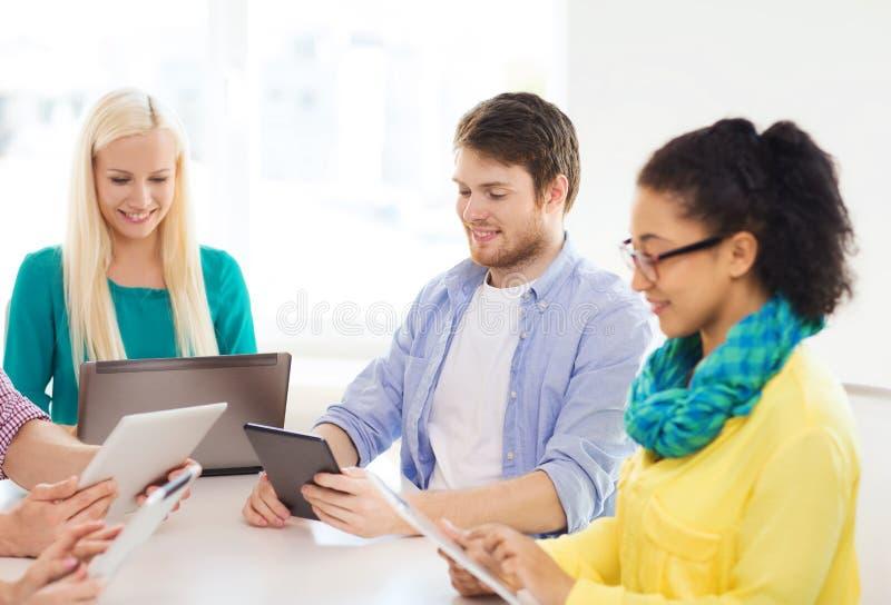 Gruppo sorridente con il pc ed il computer portatile della tavola in ufficio immagini stock