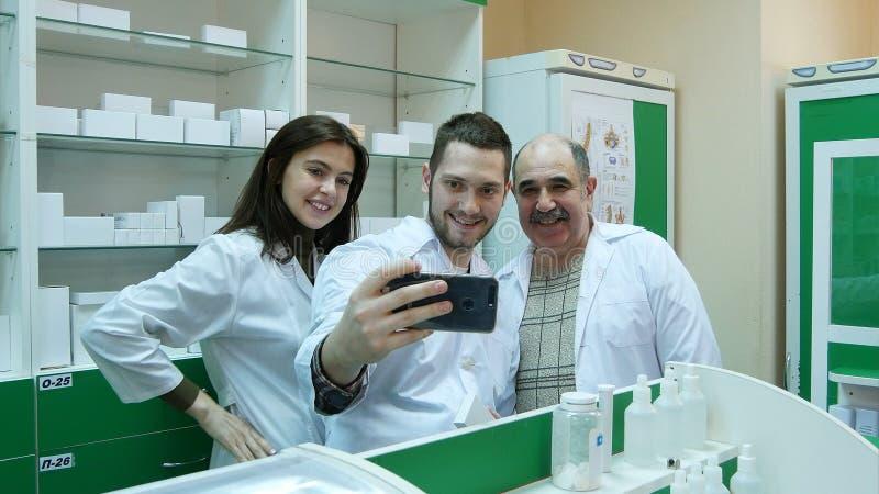 Gruppo sorridente del farmacista che prende selfie alla farmacia dell'ospedale fotografia stock