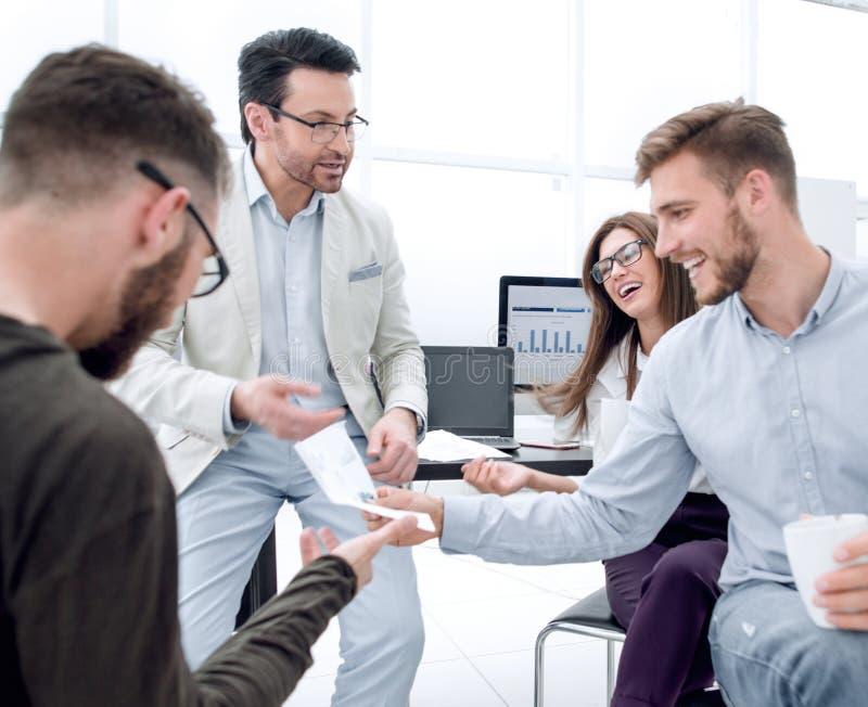 Gruppo sorridente di affari che discute i dati finanziari fotografia stock