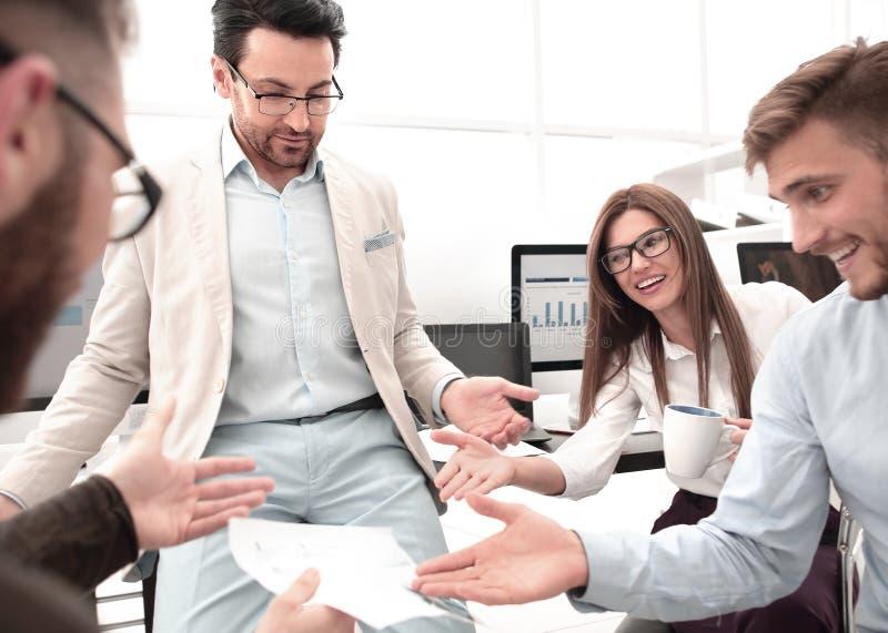 Gruppo sorridente di affari che discute i dati finanziari fotografie stock