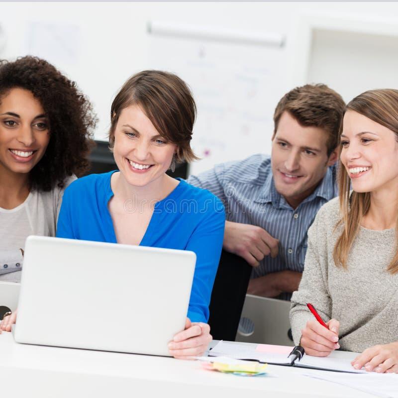Gruppo sorridente di affari raggruppato intorno ad un computer portatile immagini stock libere da diritti