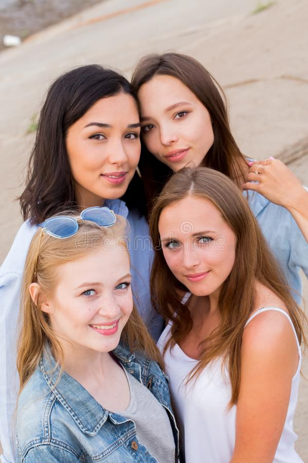 Gruppo sorridente di studentesse in vestiti di estate che posano insieme all'aperto ed esame della macchina fotografica fotografia stock libera da diritti