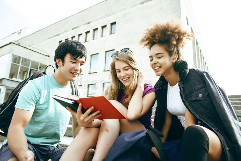Gruppo sveglio di teenages alla costruzione dell'universit? con i huggings dei libri, stile di vita degli studenti di nazioni di  fotografia stock libera da diritti